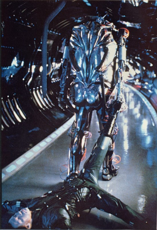 Hector drags his maker's body away in a reversal of his namesake's fate in the original legend of Achilles. This production still is notable in that it is a rare rear view of the robot's anatomical design.